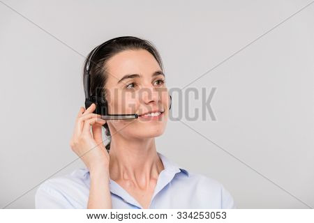 Happy young brunette operator with headset talking to clients online in front of camera in isolation