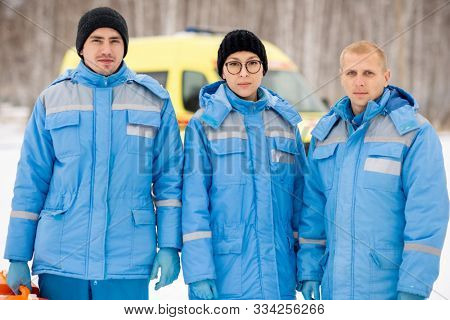 Brigade of three young paramedics in blue winter workwear and gloves standing in front of camera outdoors poster