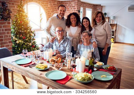 Family and friends dining at home celebrating christmas eve with traditional food and decoration, taking picture all together