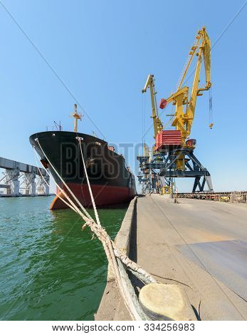 Logistics And Transportation Of Cargo Ship With Working Crane Bridge In Blue Sky Background