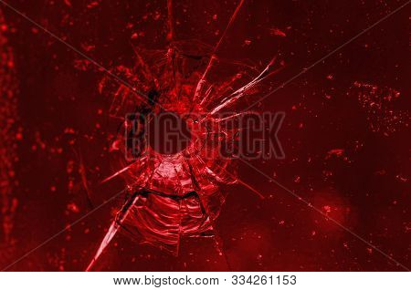Gunshot Into The Window, Red Color. Bullet Hole In Glass, Closeup, Macro. Spectacular Textured Trans