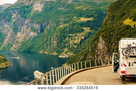 Camper car with bicycles on Flydasjuvet viewpoint and fjord Geirangerfjord with cruise ship, Norway. Travel destination. poster