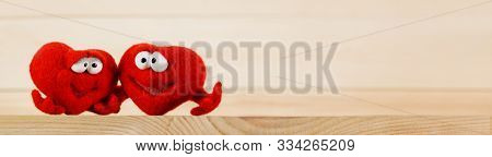 Two wool red hearts on wooden background with copy space for text, symbol of love, healtcare, valentines day concept