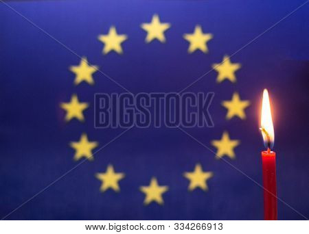Burning Candle On The Background Of The Flag Of European Union. The Concept Of Mourning And Sorrow I