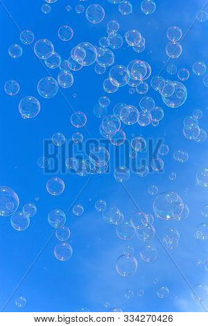 Soap Bubbles Against Blurred Blue Sky Background