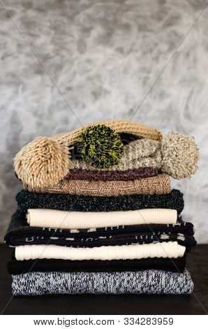 A Stack Of Neatly Folded Knitted Winter Scarves And Hats On Gray Background. Season Of Warm Clothes.