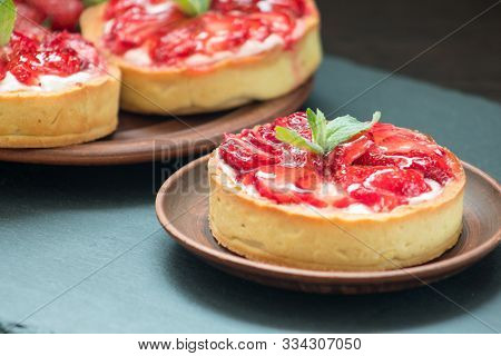 Delicious Strawberry Tarts On Table. Yummy Fruit Treat Recipe. Tasty Tartlets With Berries