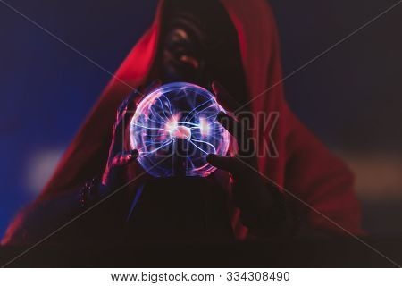 Dark Wizards Hands Are Controlling A Magic Globe, Showing Illuminating Effects.