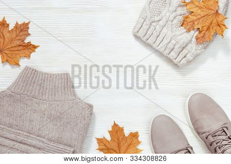 Autumn Comfortable Clothes. Warm Jacket, Suede Grey Boots, Knitted Cap On White Wooden Background. F