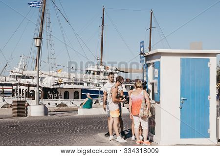 Mykonos Town, Greece - September 23, 2019: Group Of Young People Buying Bus Tickets From A Bus Stop