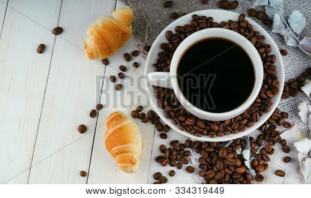 Cup Of Coffee With Coffee Beans And A Croissant On Vintage Wooden Table. Homemade Croissant Served W