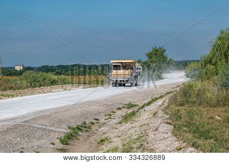 Large Dump Truck Loaded With Rocks Drive On Dust Road. Mining Industry. Heavy Equipment.