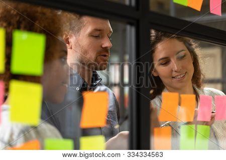 Close Up Headshot Smiling Diverse Colleagues Working Near Kanban Board.