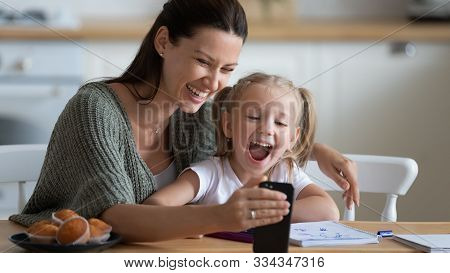Smiling Young Mother Showing Funny Cartoons To Overjoyed Daughter.