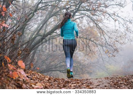 Woman Jogging Jumping In Forest, No Face. Fallen Foliage On The Ground, Autumn Foggy Morning. Flying