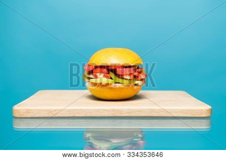 Sandwich Without Bread And Meat Lies On A Wooden Board. Burger Of Berries And Fruits