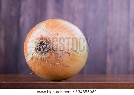 Closeup On A Whole Fresh Onion As Food Ingredient On A Wooden Table