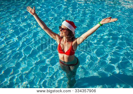 New Year And Christmas Holiday. Woman In Santas Hat And Bikini Raising Arms In Swimming Pool. Tropic