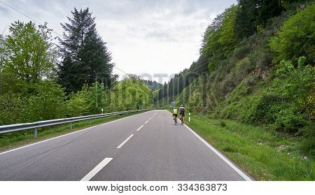 A Highway Through A Forest With Turns And Two Cyclist Riders Ride Along It. Schwarzwald Forest Road