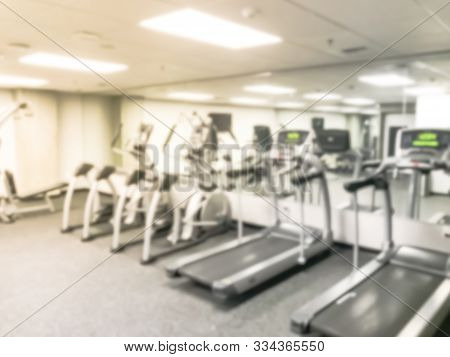 Blurry background treadmill, elliptical, strider and workout equipments at modern fitness center in USA poster
