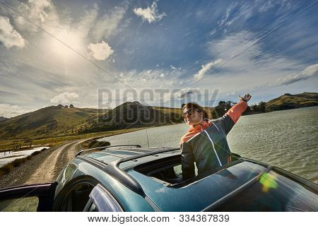 Woman leaning out through the sunroof of a car on a countryside journey on Otago Peninsula, New Zealand