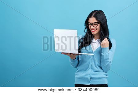 Young Woman With A Laptop Computer With Successful Pose