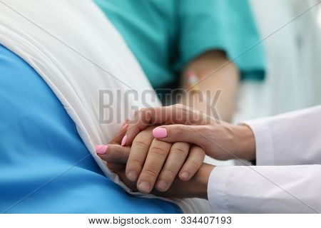Close-up Of People Holding Hands Of Each Other. Woman Calming To Sick Patient In Hospital Ward. Doc