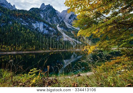 Sunny Idyllic Colorful Autumn Alpine View. Peaceful Mountain Lake With Clear Transparent Water And R