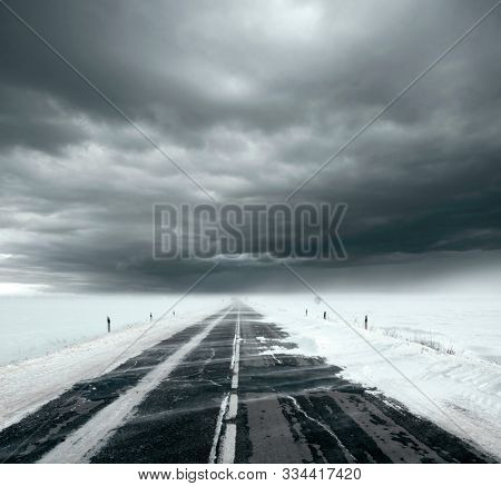 Beautiful stormy sky with clouds and snow road. Snow road in the middle of snow fields