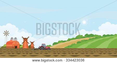 Farmer Driving A Tractor In Farmed Land And Farmhouse With Wind Mill On Rural Farm Landscape Hill Ba