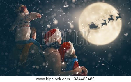 Merry Christmas and happy holidays! Cute little children with mom and dad. Santa Claus flying in his sleigh against moon sky. Family enjoying the holiday on dark background.