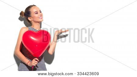 Valentine Beauty girl with red air balloon portrait pointing hand, isolated on white background. Beautiful Happy Young woman presenting products. Holiday party, birthday. Valentines's Day celebrating
