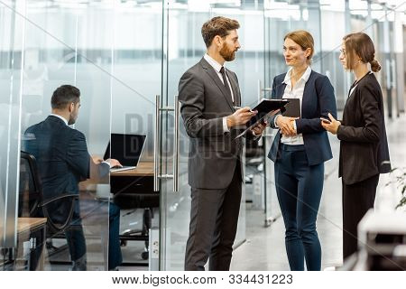 Business People Talking In The Hallway Of The Modern Office Building With Employees Working Behind G