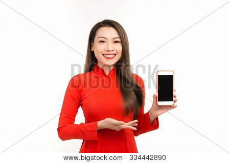 Beautfiul Woman Wearing Red Ao Dai And Showing Her Phone. Isolated Over White Background.