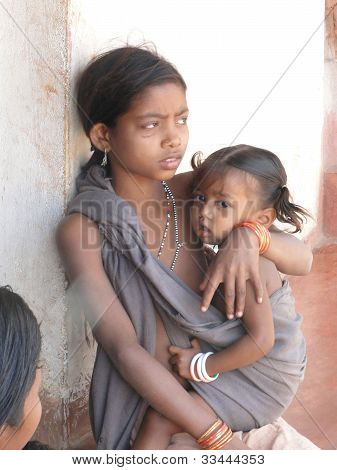 Young Tribal Girl Cares For Her Baby Sister