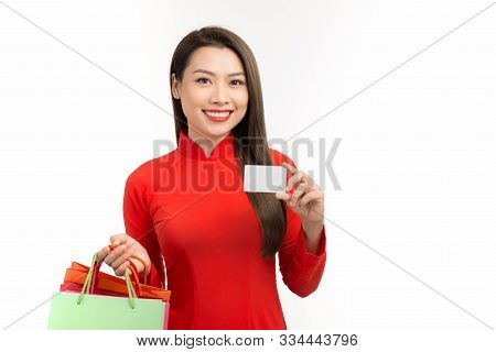 Portrait Of A Beautiful Happy Girl Holding Shopping Bags And Showing Credit Card While Wearing Ao Da