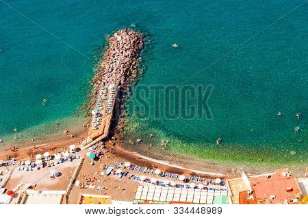 View From Above On Rocky Stones Marinas On The Beach Full Of Tourists, Deckchairs, Umbrellas On Tyrr
