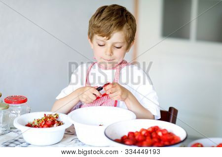 Cute Blond Kid Boy Helping And Making Strawberry Jam In Summer. Funny Child Cleaning Berries And Pre