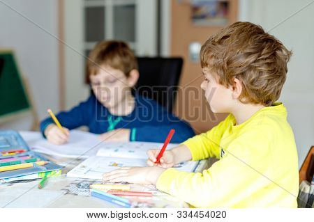 Two Little Kids Boys At Home Making Homework. Little Concentrated Children Writing With Colorful Pen