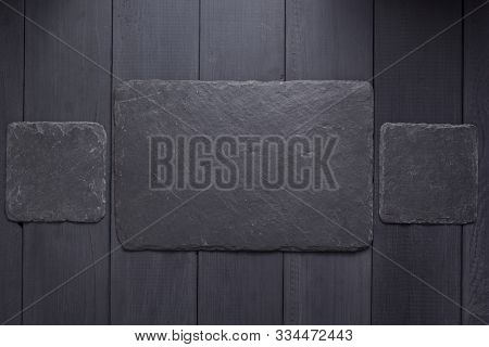 slate stone nameplate or wall sign at black wooden background texture surface, with screws