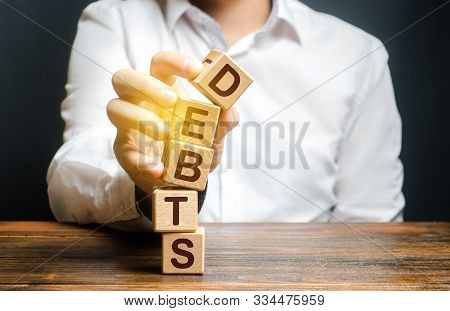 A Man Breaks A Tower Of Blocks With The Word Debts. Reduction Or Restructuring Of Debt. Bankruptcy.