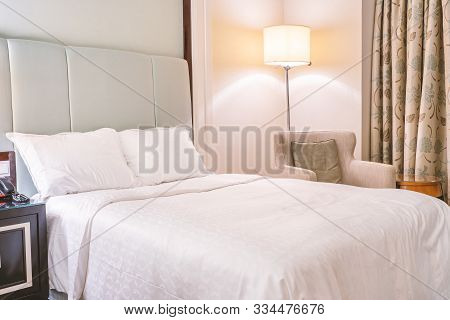 Clean And Cozy Modern Hotel Bedroom Interior, Warm Tone Room With A Standing Lamp, Linen Sofa With A