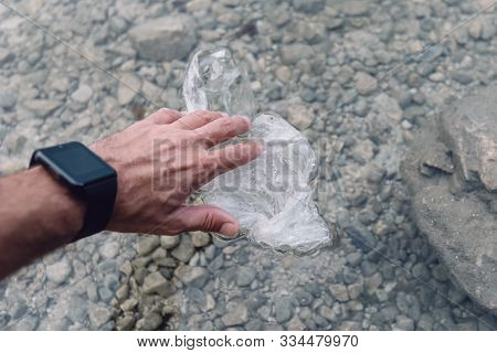 Environmentalist Taking Plastic Bag From Water, Close Up Of Hand