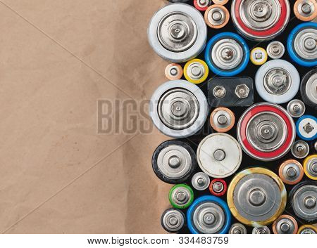 Used Alkaline batteries of different types (C AA AAA D 9V) on wrinkled recycled paper sorted for recycling - toxic waste and environmental issues background