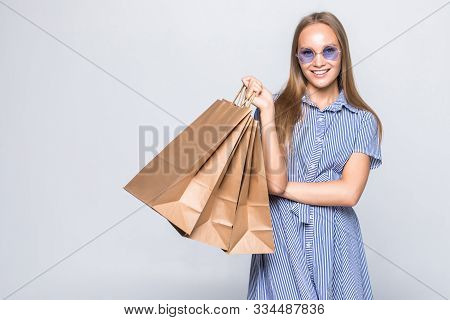 Beautiful Young Woman With Purchases In Hands After Shopping Isolated On Gray Background