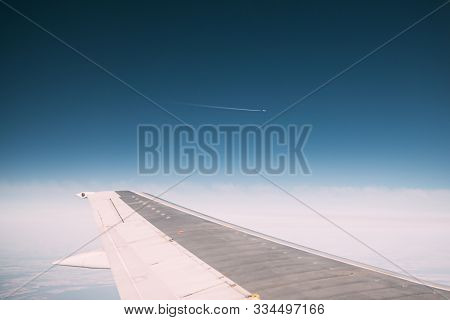 Contrail In Blue Sky. Plane In Sunny Sky. Aircraft In Sky With Plane Trail. View From Airplane Windo