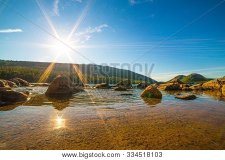 Sun Shining Over Watery Rocks With The Bubbles In The Background On Jordon Pond In Acadia National P