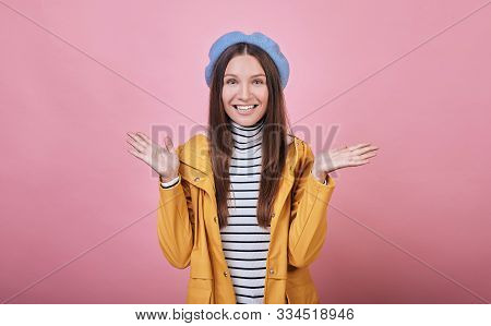 Cool Young Girl In A Blue Barret, A Striped Blouse And A Yellow Rain Jacket Smiles Cute Against A Pi