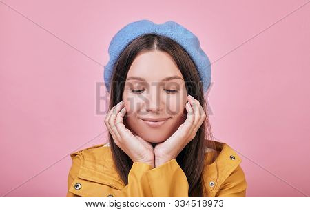 Cool Cute Tender Girl In A Gentle Blue Barret, A Striped Blouse And A Yellow Rain Jacket Smiles Cute