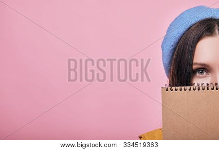 Cool Teenager With Dark Hair In Blue Barret And Yellow Raincoat Is Standing With A Brown Notebook. L